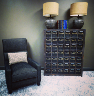 Rushmore accent chair by Jonathan Louis with apothecary cabinet and ceramic lamps