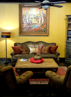 Trent sofa by Paul Robert with vintage Turkish rug, antique hand-carved coffee table and tufted bootstrap leather chairs